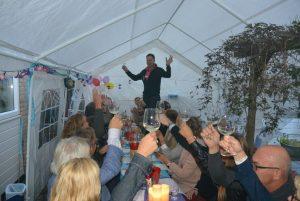 Wijnproeverij met familie en vrienden tijdens feest in Amstelveen. De jarige proost op de tafel.